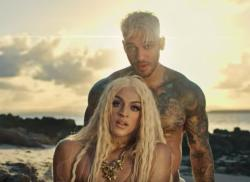 "Lucas Lucco stands behind Pabllo Vittar in the music video for ""Pariso."""