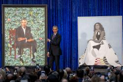 Former President Barack Obama, center, stands on stage during the unveiling of the Obama's official portraits at the Smithsonian's National Portrait Gallery.