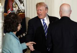 President Donald Trump is greeted by Secretary of Transportation Elaine Chao, left, and Nebraska Gov. Pete Ricketts, right.