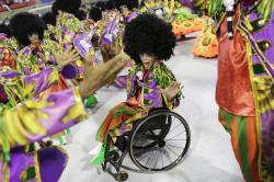 Performer from the Academicos do Grande Rio samba school parade on her wheel chair during Carnival celebrations at the Sambadrome in Rio de Janeiro, Brazil.