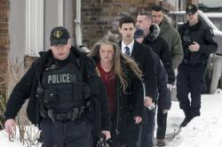 Forensic anthropologist professor Kathy Gruspier, second from left, walks with police officers at a property where alleged serial killer Bruce McArthur worked in Toronto.