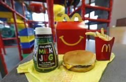 A Happy Meal featuring non-fat chocolate milk and a cheeseburger with fries.