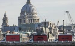The Community-led organisation, Justice4Grenfell, parades three billboards backdropped by St. Paul's Cathedral as they move around London, Thursday Feb. 14, 2018.