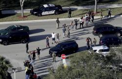 In a Wednesday, Feb. 14, 2018 file photo, students hold their hands in the air as they are evacuated by police from Marjory Stoneman Douglas High School in Parkland, Fla.