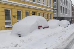 Snow-covered cars are parked in a street in Flensburg, Germany.