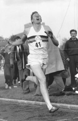 In this May 6, 1954 file photo, Britain's Roger Bannister hits the tape to break the four-minute mile in Oxford, England.