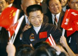In this Oct. 31, 2003, file photo, school children wave Chinese and Hong Kong flags as they welcome China's first astronaut Yang Liwei, center, to Hong Kong's Government House for an official reception hosted by Hong Kong's Chief Executive Tung Chee-hwa, shortly after arriving for a five-day visit to the territory