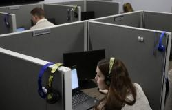 """In this Nov. 8, 2017, photo, Jessica McShane, an employee at Interactions Corp., foreground, monitors person-to-computer communications, helping computers understand what a human is saying, in the """"intent analysis"""" room at the company's headquarters in Franklin, Mass."""