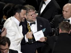 """Jimmy Kimmel, left, congratulates Guillermo del Toro in the audience after winning the award for best picture for """"The Shape of Water"""" at the Oscars."""
