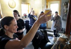 In this Sunday, March 4, 2018, photo, Elizabeth Bove, of Woodstock, Conn., left, joins with others as they raise their glasses in a toast after helping brew a batch of beer at Black Pond Brews brewery, in Danielson, Conn.
