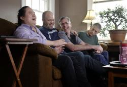 Wil Darcangelo, second from left, and his husband, Jamie, laugh with their 22-year-old adopted daughter, Lavender, who is blind and autistic, at their home in Fitchburg, Mass.