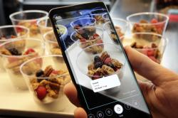 In this Feb. 21, 2018, file photo the Bixby virtual assistant software of a Samsung Galaxy S9 Plus mobile phone identifies food and displays its calorie content during a product preview in New York