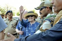 Former U.S. Secretary of State Hillary Clinton, center, waves as she comes out of the Jodhpur airport upoon her arrival in Jodhpur, Rajasthan state, India.
