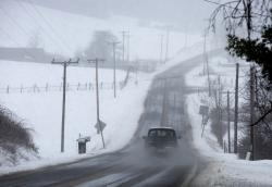 A vehicle drives through snow on Bent Mountain Road near Snake Drive in Copper Hill, Floyd County, Va.