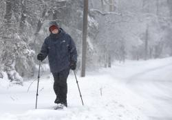 Joe Donaghey, of Norwell, Mass., snowshoes along a road during a storm.