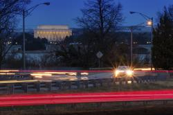 Traffic streaks along U.S. Highway 50 early in the morning, Friday, March 30, 2018 across the Potomac River from Washington in Arlington, Va.