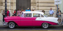 Tourists look at a classic American car parked beside the cruise ship terminal in Havana, Cuba.