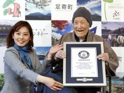 Masazou Nonaka, right, receives the certificate from Guinness World Records as the world's oldest living man at age 112 years and 259 days during a ceremony in Ashoro on Japan's northern main island of Hokkaido.