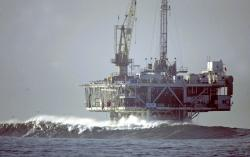 In this Dec. 21, 2005, file photo, waves break by an oil platform that's offshore from Seal Beach, Calif.