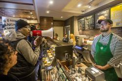 Local Black Lives Matter activist Asa Khalif, left, stands inside a Starbucks, Sunday April 15, 2018, demanding the firing of the manager who called police resulting the arrest of two black men on Thursday.