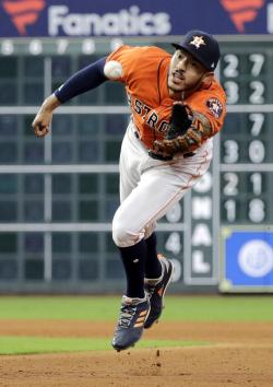 Houston Astros shortstop Carlos Correa tosses the ball with his glove to first baseman Yuli Gurriel after fielding a ground ball by Texas Rangers' Nomar Mazara during the eighth inning of a baseball game Friday, April 13, 2018, in Houston.
