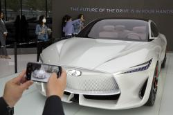 In this April 19, 2018, photo, visitors look at the Infiniti electric concept sedan at a showroom ahead of the Auto China 2018 to be held in Beijing, China
