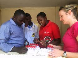 In this undated photo provided by CDC.gov, Dr. Aimee Summers organizes the blood sample collection containers with Kenyan lab technicians at the International Rescue Committee medical clinic in Kakuma Refugee Camp, Kenya