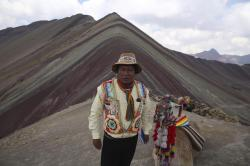 Gabino Human poses for a photo backdropped by Rainbow Mountain, in Pitumarca, Peru.