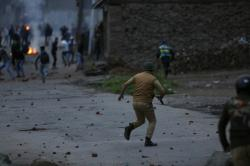 An Indian police officer chases stone throwing Kashmiri protesters in Srinagar.