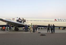 Passengers stand on the tarmac of Denver International Airport after being evacuated from a Delta flight from Detroit.