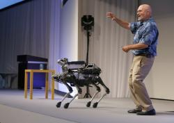 In this July 20, 2017 file photo, Boston Dynamics Chief Executive Marc Raibert speaks about his four-legged robot SpotMini during a SoftBank World presentation at a hotel in Tokyo