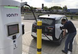 In this Friday, May 11, 2018 photo a man charges his BMW electric vehicle at the rest stop Brohltal Ost at the A61 motorway in Niederzissen, Germany