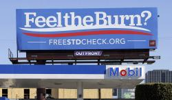 "This April 1, 2016 file photos shows a billboard above a gas station that reads ""Feel The Burn,"" a play on then-presidential candidate Bernie Sanders' campaign slogan, ""Feel The Bern."""