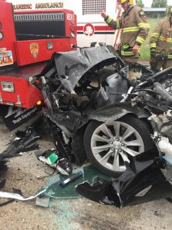 In this Friday, May 11, 2018, photo released by the South Jordan Police Department shows a traffic collision involving a Tesla Model S sedan with a Fire Department mechanic truck stopped at a red light in South Jordan, Utah