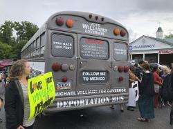 """A Georgia gubernatorial candidate touring the state in a """"deportation bus"""" is greeted with protests by immigrants and other residents in Clarkston, Ga., Wednesday, May 16, 2018"""