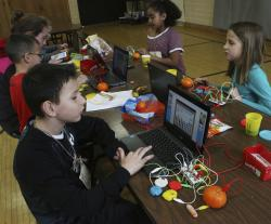 Students attach wires to Play-Doh to make a working keyboard during the Keicher Elementary Tech Day in Jackson, Mich.
