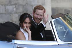 The newly married Duke and Duchess of Sussex, Meghan Markle and Prince Harry, leave Windsor Castle in a convertible car after their wedding in Windsor, England, to attend an evening reception at Frogmore House.