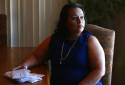 Josephine Rizo sits in her home with her stack of bills from her ongoing battle with cancer in Phoenix.