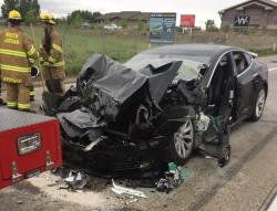 In this Friday, May 11, 2018, file photo released by the South Jordan Police Department shows a traffic collision involving a Tesla Model S sedan with a Fire Department mechanic truck stopped at a red light in South Jordan, Utah