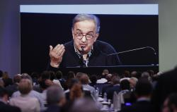 Journalists watch a giant screen as Fiat Chrysler CEO Sergio Marchionne speaks during the 'Capital market day' at the FCA headquarters in Balocco, Italy, Friday, June 1, 2018