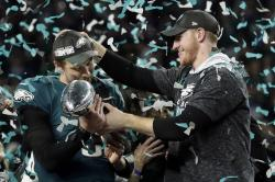 Philadelphia Eagles quarterback Carson Wentz, right, hands the Vincent Lombardi trophy to Nick Foles after winning the NFL Super Bowl 52 football game against the New England Patriots in Minneapolis.