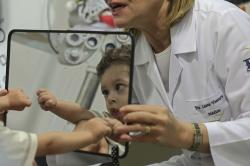 In this May 3, 2018 photo, 2-year-old Luiz Mauricio, who was born with the Zika-caused microcephaly birth defect, is reflected in a mirror held by Dr. Liana Ventura during an ophthalmology exam at the Altino Ventura Institute, in Recife, Brazil
