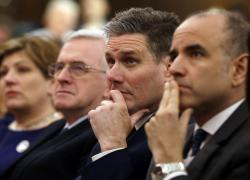In this London, Friday, Feb. 24, 2017 file photo, Keir Starmer, second right, of the Labour party listens to Leader of the opposition Labour Party Jeremy Corbyn's speech laying out the plan for the party following the Brexit vote in June 2016