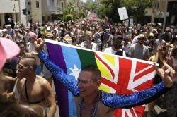 Israelis and tourists wave flags as they participate in the Gay Pride parade in Tel Aviv, Israel.