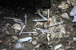 This Feb. 2, 2017 file photo, shows used needles littering the ground along train tracks in Philadelphia's largest open air drug market in the Kensington section of the city
