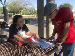 In this June 5, 2018, photo, mathematics teacher Heather LaBelle, seated, shows Roger Baker how to gather signatures for the Invest in Education Act, a proposal to raise money on high earners to fund public education in Phoenix, Ariz.
