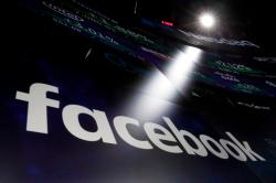 In this March 29, 2018, file photo the logo for Facebook appears on screens at the Nasdaq MarketSite in New York's Times Square