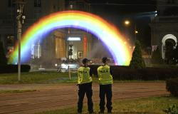 Police officers stand next to a light and water rainbow installation on the night before a gay pride parade, in downtown Warsaw, Poland, Friday, June 8, 2018