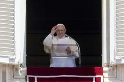 Pope Francis waves to the crowd as he recites the Angelus noon prayer from the window of his studio overlooking St. Peter's Square, at the Vatican.