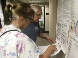 In this Tuesday, June 5, 2018 photo, Dave and Jane Will inspect a sample ballot in Bismarck, N.D.